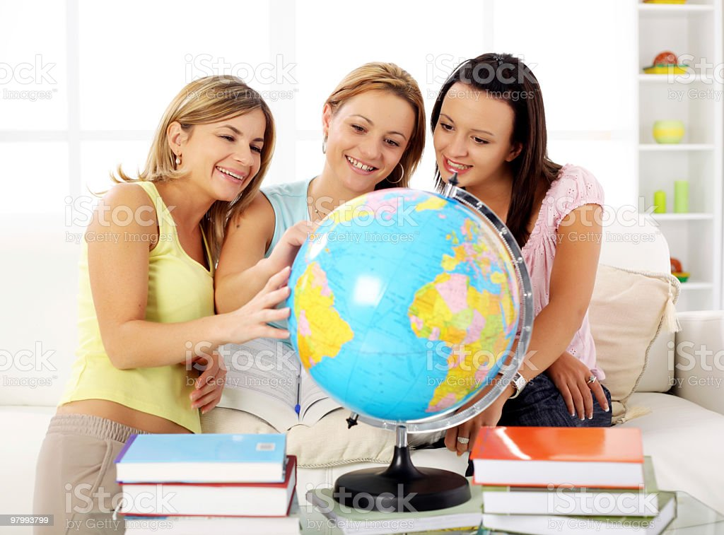 Young women choosing  travel destination on the globe. royalty-free stock photo