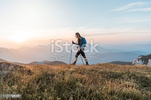 Young woman with a backpack hiking in the mountains. Exploring in the nature, enjoying the view.