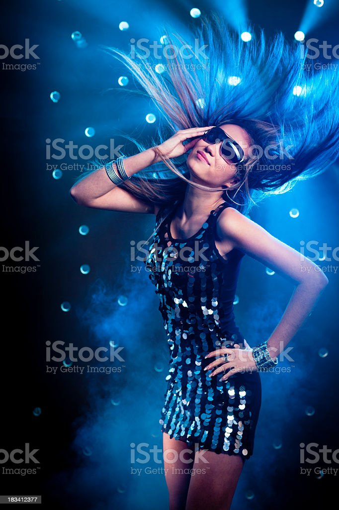 Young women dancing on smoky disco background