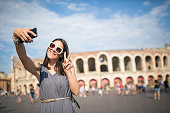 Young women discovering Italy-Verona, walking on the street, taking selfie