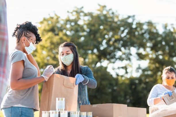 mujeres jóvenes discuten contenido de bolsa en food drive - giving tuesday fotografías e imágenes de stock
