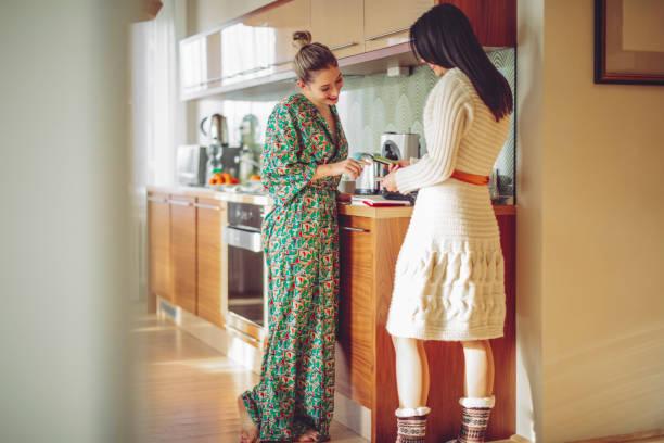 junge frauen diskutieren in der küche - strickmantel stock-fotos und bilder