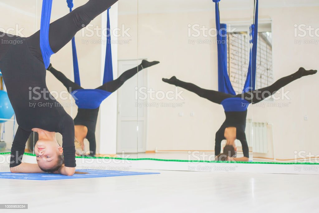 Young women doing aerial yoga exercise or antigravity yoga stock photo