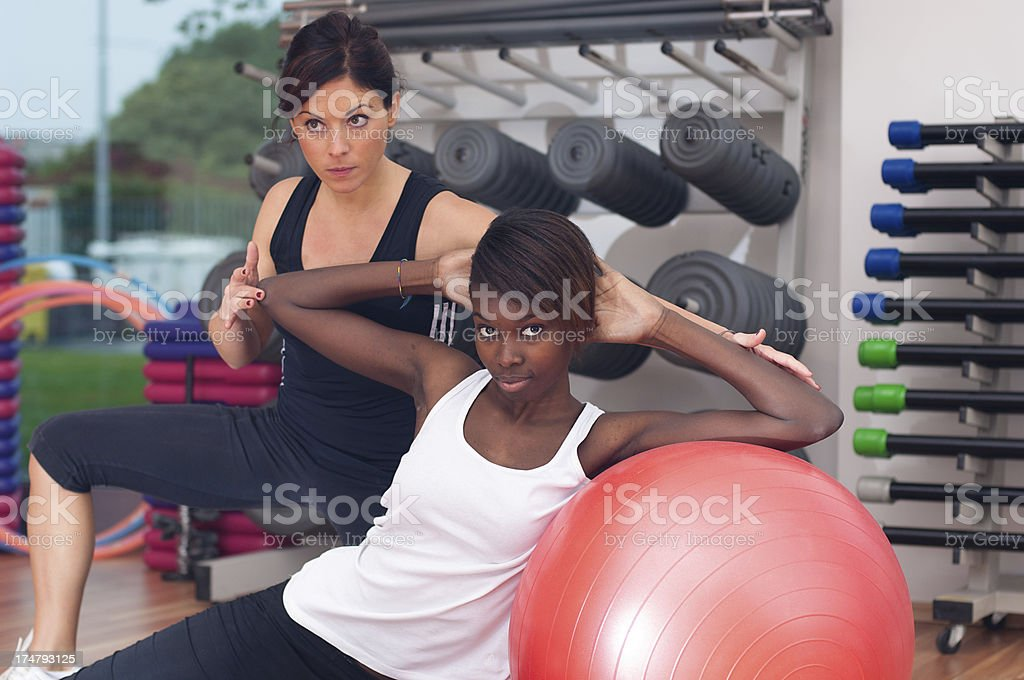 Young Women Doing Exercises with her Personal Trainer at Gym royalty-free stock photo