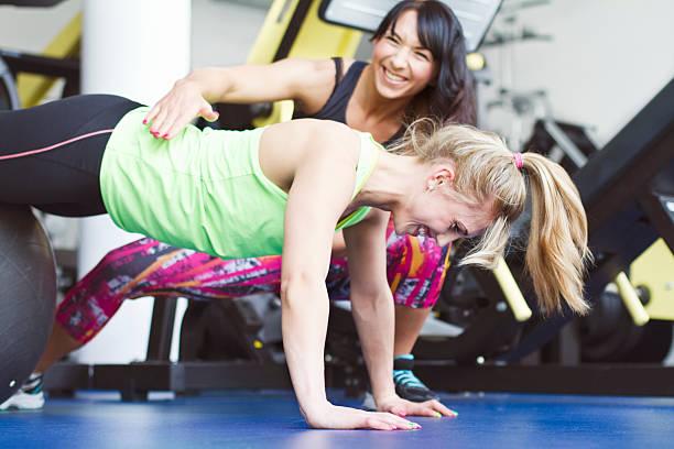 Młode kobiety robienie pompek w siłowni – zdjęcie