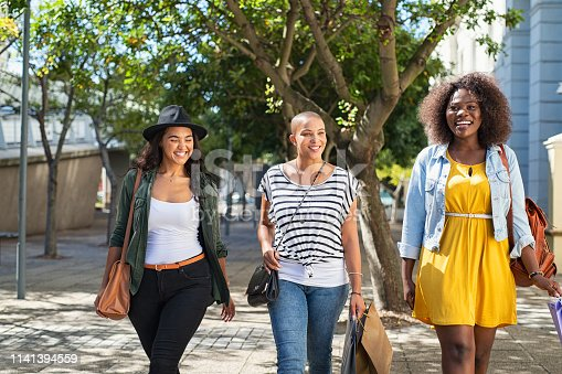 Three beautiful women friends walk on street after shopping. Best friends girls meeting while shopping. Three stylish and trendy women talking and laughing outdoor in the city.