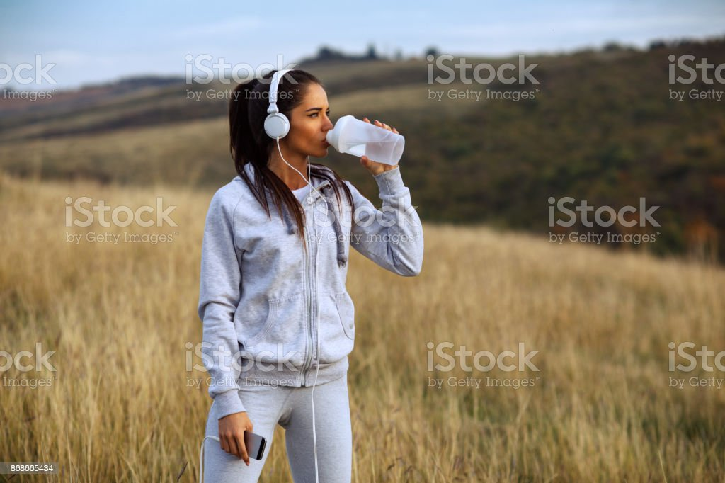 Young women drink water after jogging in nature stock photo