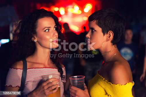 Young women drinking beer and making faces at the live concert on a summer night.