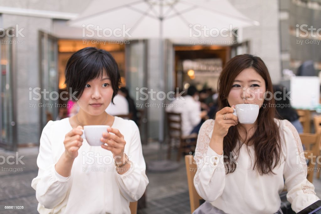 Young women drinking coffee after lunch royalty-free stock photo