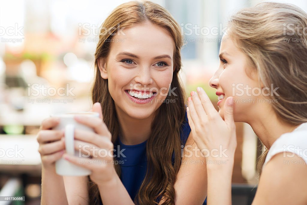 young women drinking coffee and talking at cafe stock photo