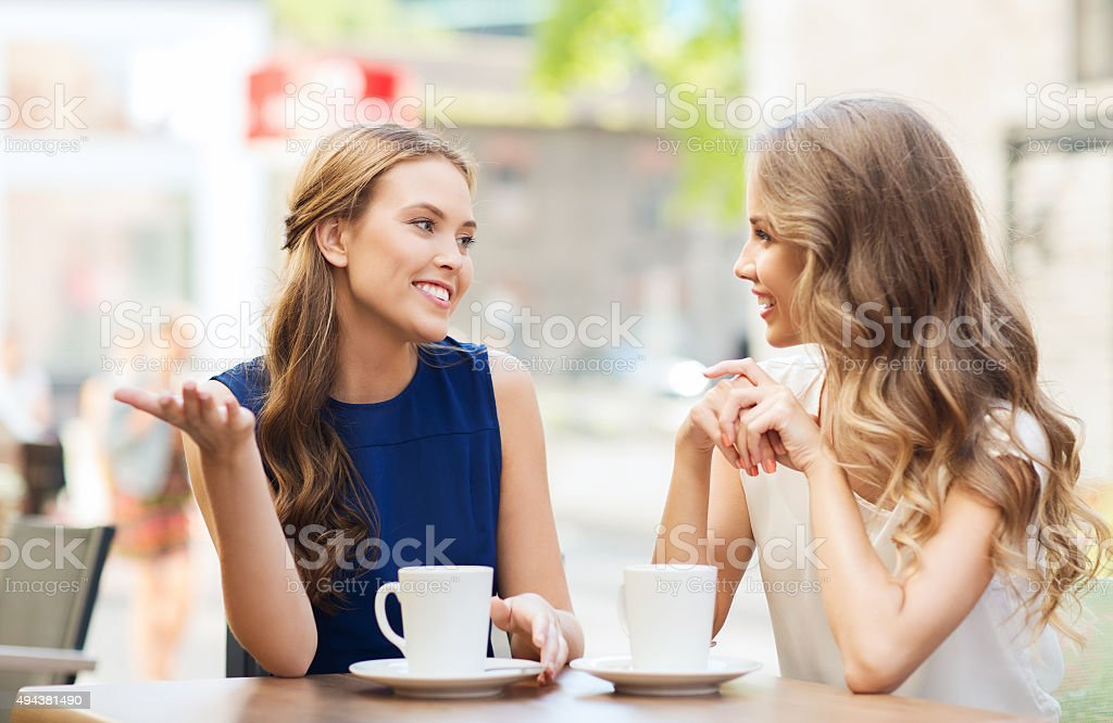 young women drinking coffee and talking at cafe royalty-free stock photo