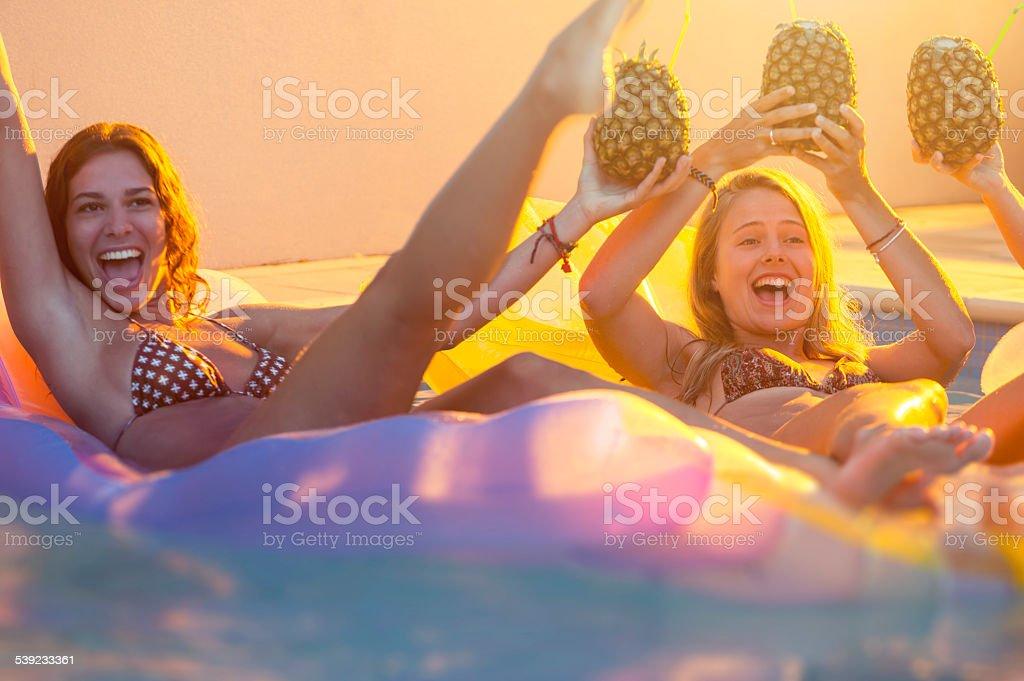 Mujeres bebiendo en lilos en fiesta junto a la piscina. foto de stock libre de derechos