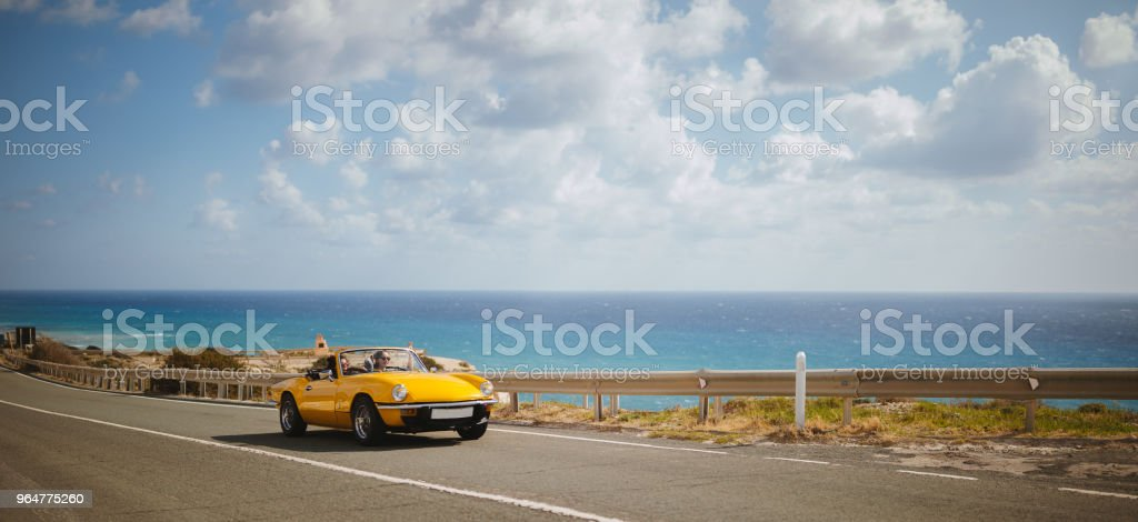 Young women driving retro convertible car on seaside highway royalty-free stock photo