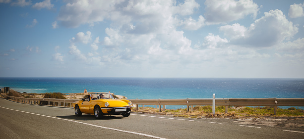 Young hipster women on summer holidays driving yellow vintage convertible car by the sea