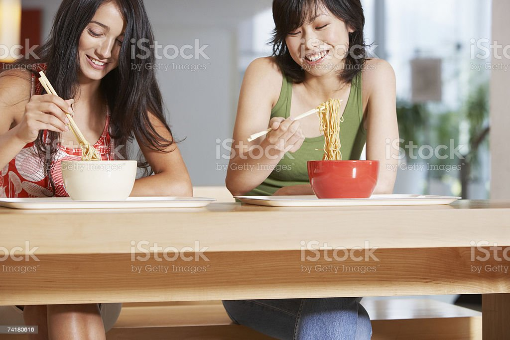Young women eating bowl of noodles with chopsticks in cafeteria royalty-free stock photo
