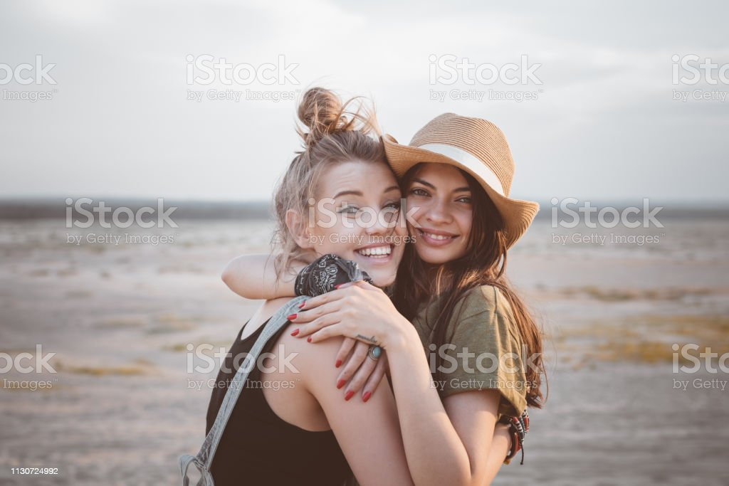 Young women embracing in desert against sky Portrait of smiling young women embracing in desert. Multi-ethnic female friends are standing against sky. They are enjoying vacation together. 20-24 Years Stock Photo