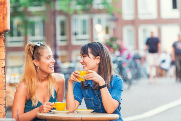 jonge vrouwen die genieten van een kopje koffie - keizersgracht stockfoto's en -beelden