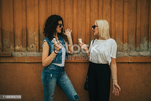 1092709104 istock photo Young women enjoying a day in the city and eating ice cream 1155055203