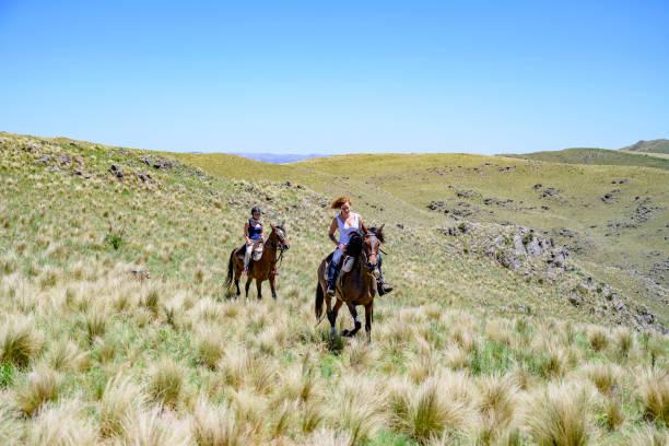 Young women enjoying Argentine trail riding on horseback stock photo