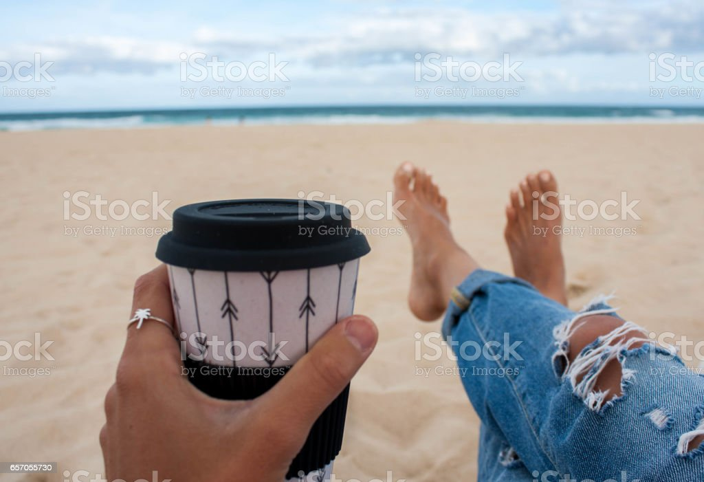 Young Women enjoying her coffee on the beach stock photo