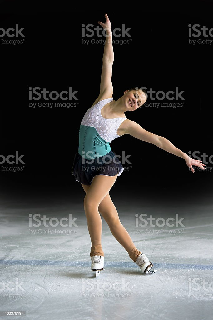Young Women Figure Skating on Black Background stock photo