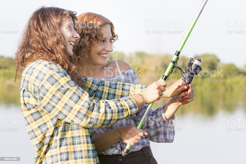 Young women fishing at river royalty-free stock photo