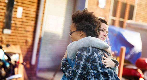 Young women forgiving each other with a hug Young women forgiving each other with a hug in an alley. Tthey are both dressed in casual urban clothing. Photographed at sunset in Brooklyn. Letterbox format. apologist stock pictures, royalty-free photos & images