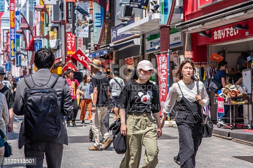 Tokyo, Japan - May 26, 2019: Young women friends enjoy shopping at the famous Ameyoko or Ameya Yokocho market, in Asakusa, near Ueno Park. The market is known for great prices and local cuisine.