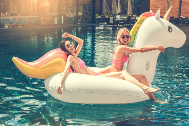 young women friends in the swimming pool fun - unicorns stock photos and pictures