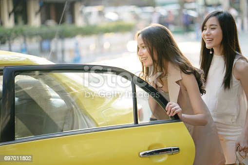 istock Young women getting a taxi after shopping 697011802