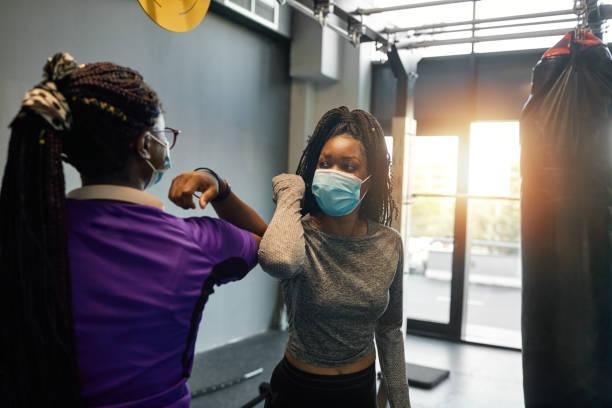 Young Women Greeting In Gym During Coronavirus Pandemic, Elbow Bump stock photo
