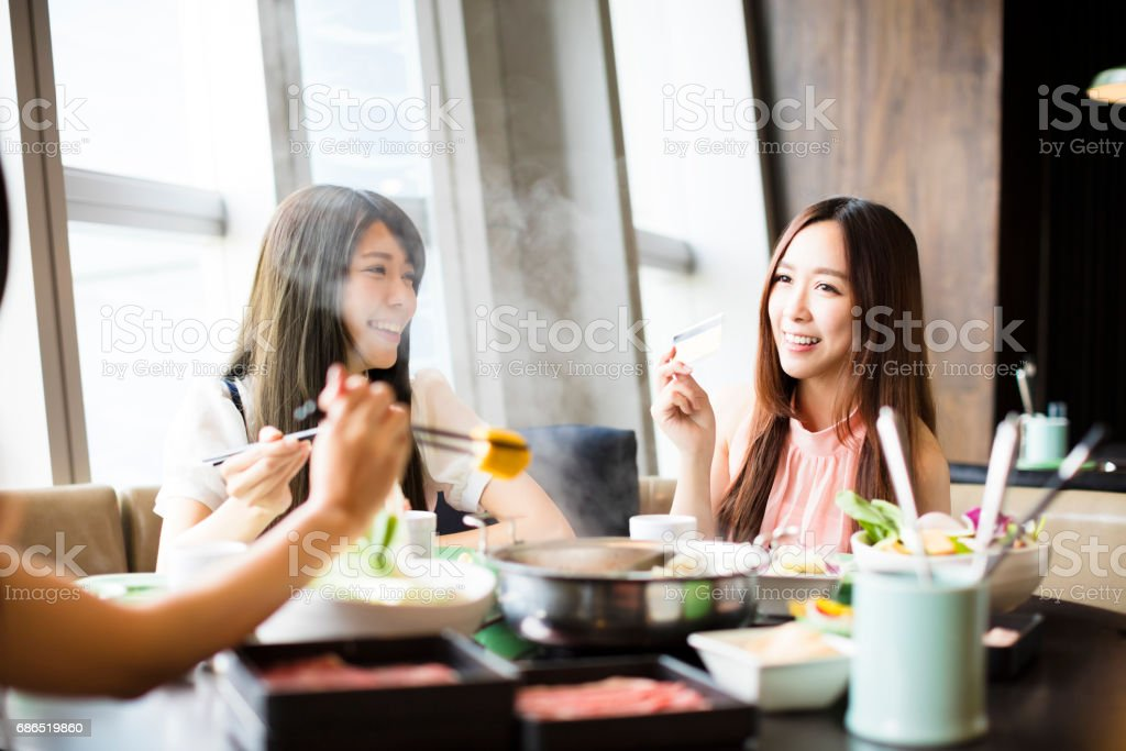 young Women group  Eating hot pot and showing credit card stock photo
