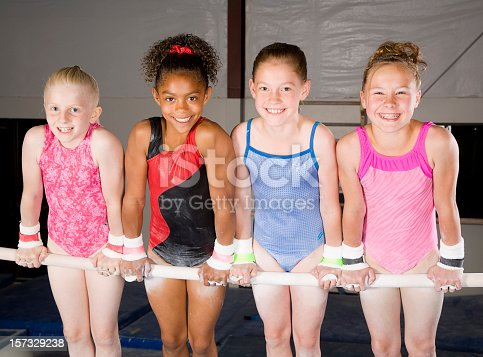 Four young gymnasts balancing on the parallel bars.