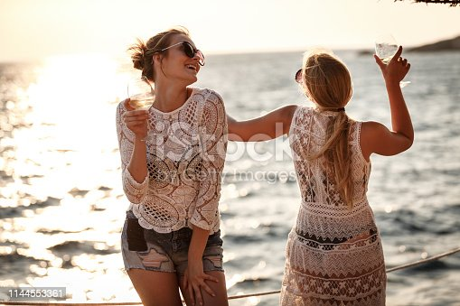 Two young women are dancing and having wine at the beach.