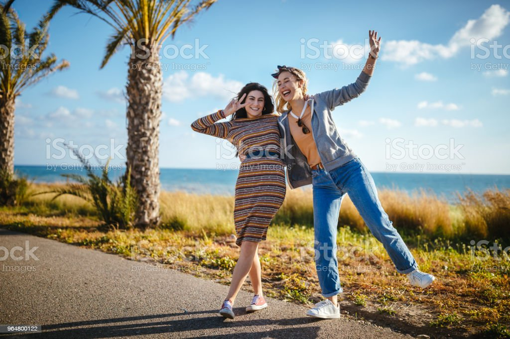 Young women having fun by the side of the road royalty-free stock photo