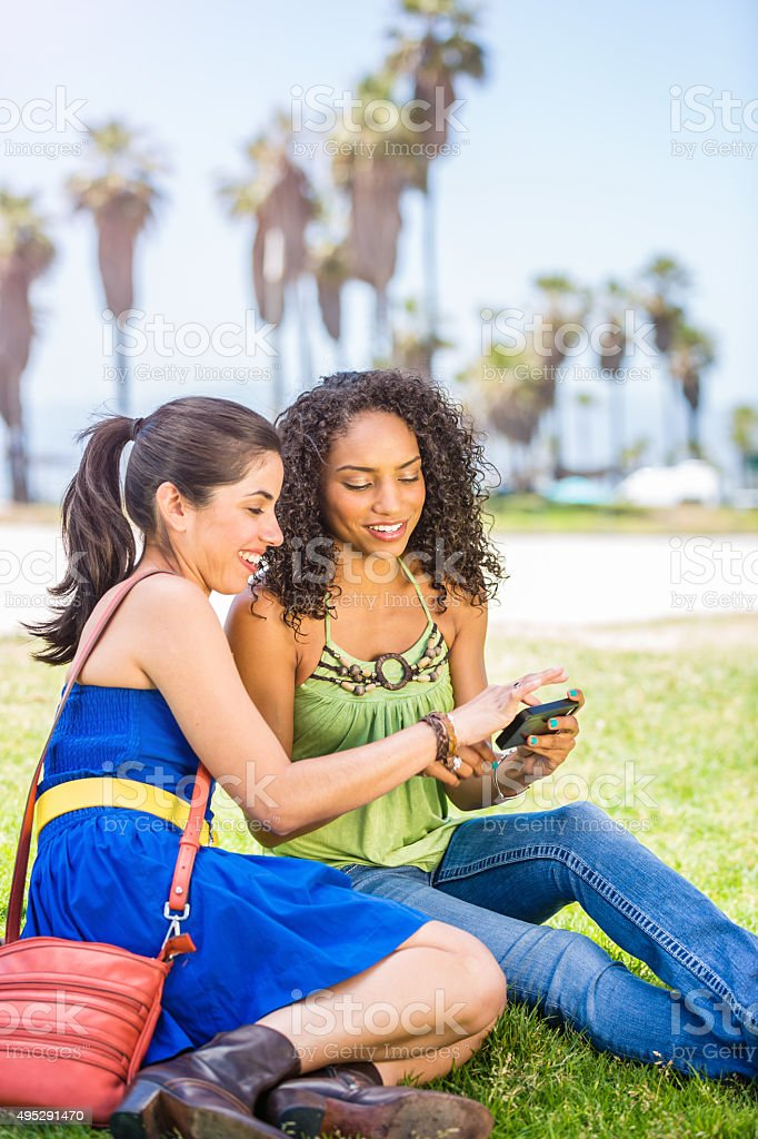 Young women having fun with smart phone stock photo