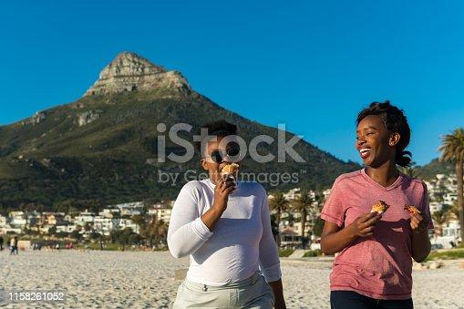 istock Young women having ice creams at beach 1158261052