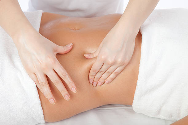 young women having stomach massage - human abdomen stock pictures, royalty-free photos & images