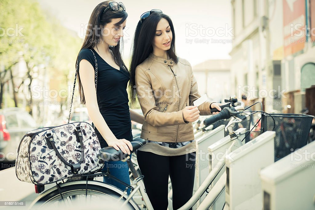 Young Women Hiring Public Bicycles stock photo