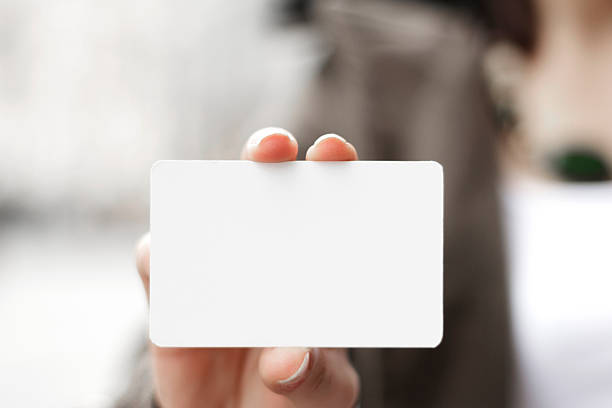 young women holding a blank card in hands - gift voucher or card stock photos and pictures