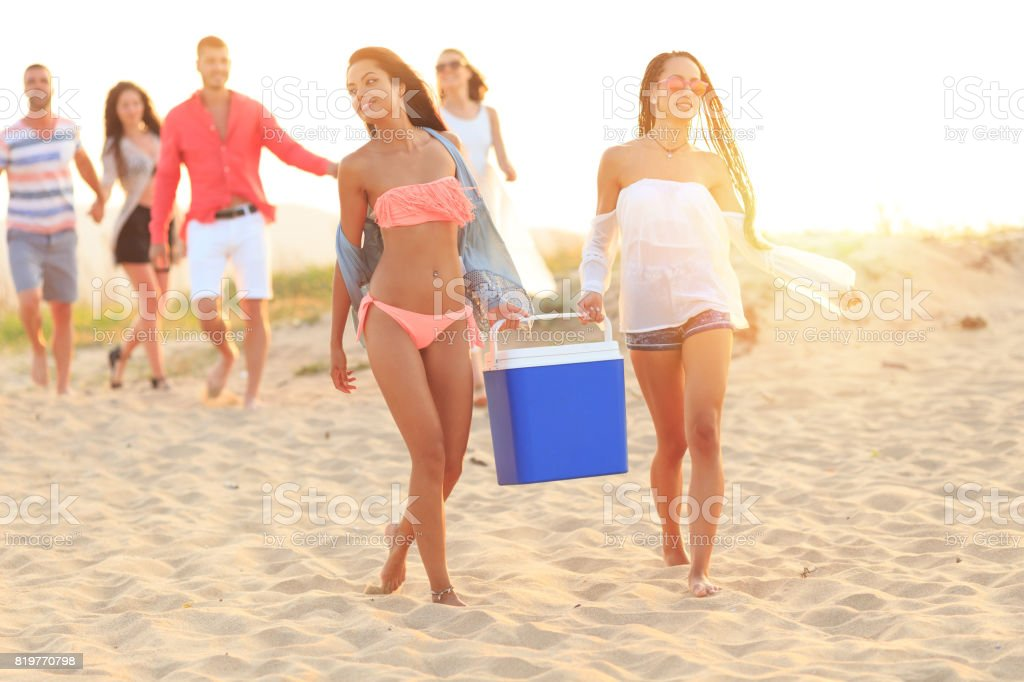 Young women holding cooler box on beach stock photo