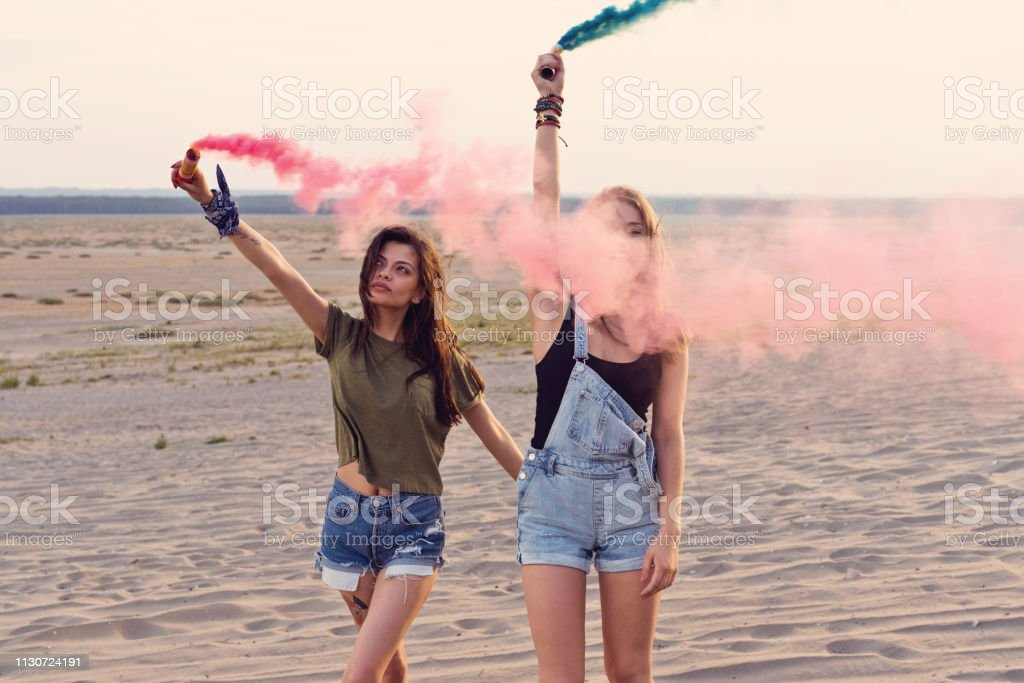 Young women holding distress flares at desert Young women holding distress flares at desert. Beautiful female friends are enjoying together during vacation. Hipsters are hiking and having fun on sand. 20-24 Years Stock Photo