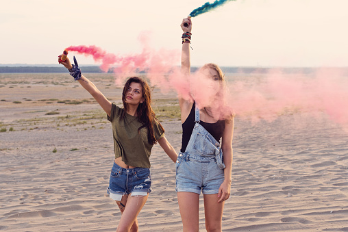 Young Women Holding Distress Flares At Desert Stock Photo - Download Image Now