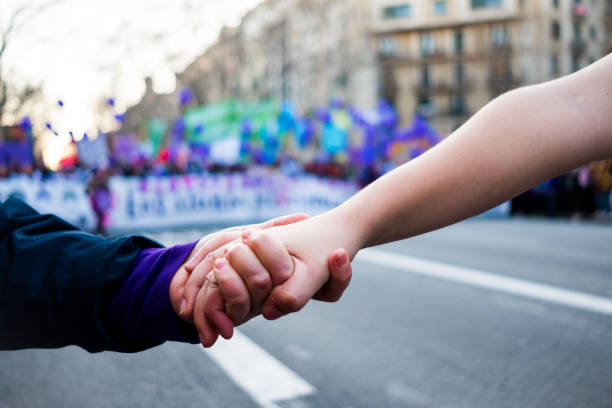young women holding hands during woman's day rally with purple balloons in background for women rights and feminism stock photo