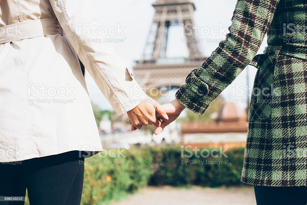 Young women holding hands in front of Eiffel Tower royalty-free stock photo