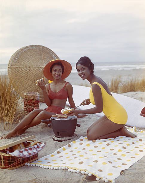 Young women holding hot dog on beach, smiling stock photo