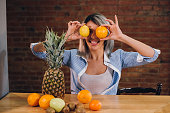 Young women holding up orange and lemon to eyes, and making face grimace, in the kitchen with brick wall, she wear blue casual shirt.