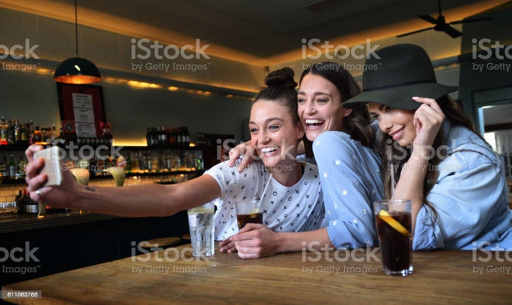 Young women in bar taking selfie stock photo