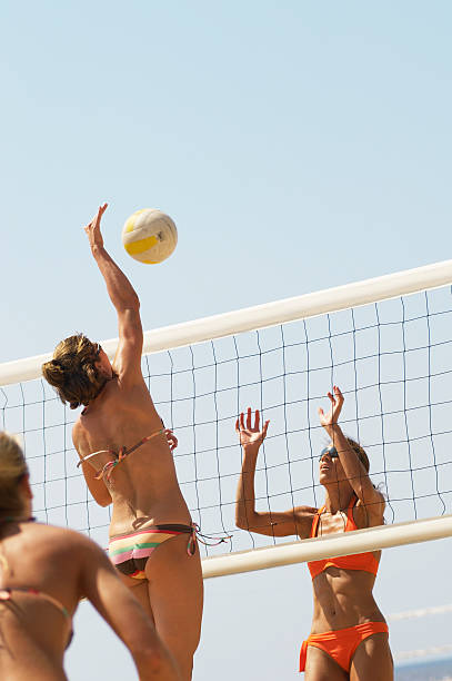 Young Women in Bikinis Playing Volleyball stock photo