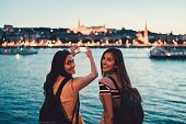 Best friends on a vacation in Budapest taking photos with smartphone